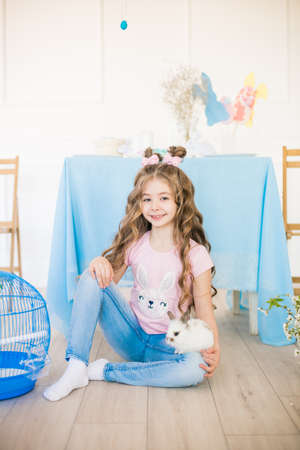 Little cute girl with little bunnies and Easter decor at home