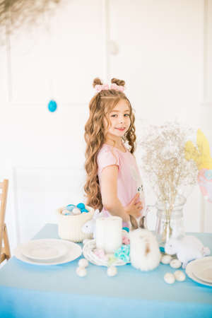 Little cute girl with little bunnies and Easter decor at home Stock Photo - 127402444