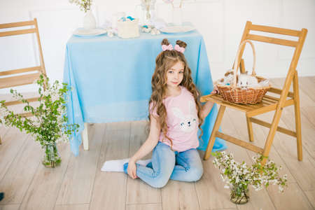 Little cute girl with little bunnies and Easter decor at home Stock Photo - 127402495