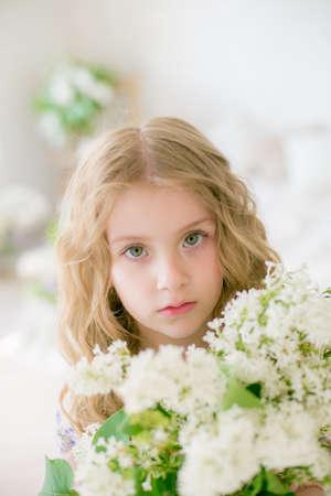 petite fille aux cheveux blonds avec des fleurs lilas Banque d'images