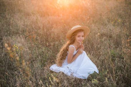 little girl in a summer field at sunset