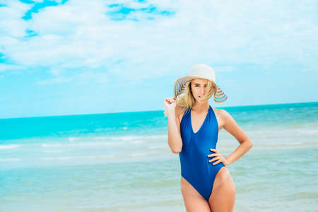 A beautiful young girl in a blue swimsuit on beach