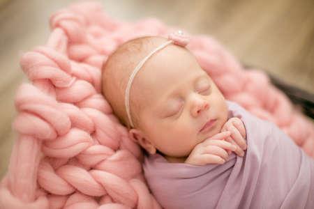 petite fille nouveau-née en couverture rose dans un panier en osier décoré de belles tulipes roses printanières