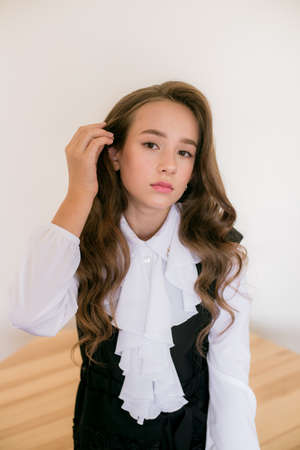 Cute girl with long curly hair in school fashion clothes. School fashion in vintage elite style. Фото со стока