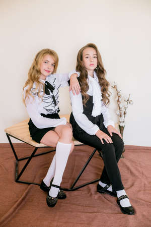 Two cute girls schoolgirls with long curly hair in fashionable school clothes. School fashion in vintage elite style.