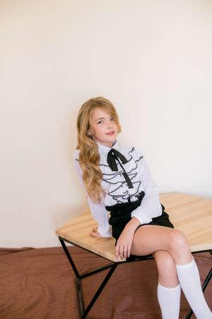 Ragazza carina con lunghi capelli ricci biondi in vestiti di moda della scuola. Moda scolastica in stile vintage d'élite. Archivio Fotografico