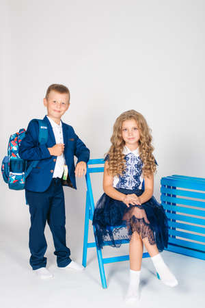 Boy and girl schoolchildren in fashionable school clothes with a school bag on a white background Standard-Bild
