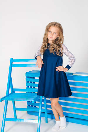 Cute girl with blond curly hair in school fashion clothes with blue chair on a white background