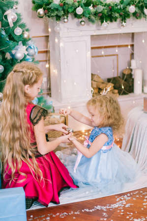 Cute girls with blond hair in a white ball gown by the Christmas tree in holiday dresses with gifts and silver confetti. Christmas mood
