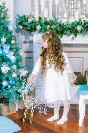 Cute girl with long hair in a white ball gown by the Christmas tree in holiday dresses with gifts and silver confetti. Christmas mood Stock Photo