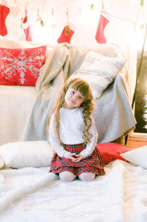 Cute girl with long hair in the room with Christmas decorations and gifts. Christmas mood