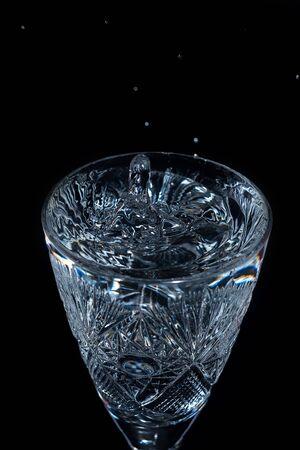 Water drop splashes in wineglass photo