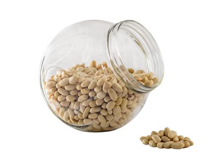 tare: Raw peanuts drops out big glass tare Stock Photo