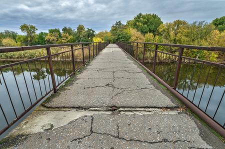 Bridge points to an autumn forest Banco de Imagens