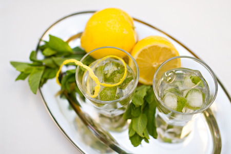 champaigne: Photo of Two cocktail glasses and mint with lemons on tray
