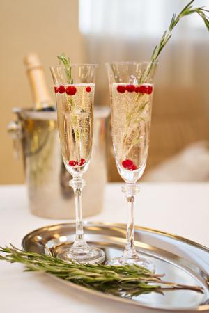 シャンパン ボトルとシャンパンと皿にローズマリーの 2 つのメガネの写真