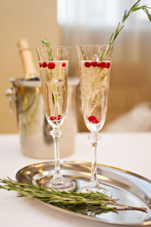 Photo of Two glasses of Champagne and rosemary on a plate with a bottle of Champaign Zdjęcie Seryjne