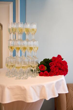 champaigne: Glasses of champaigne and a wedding bunch of roses Stock Photo