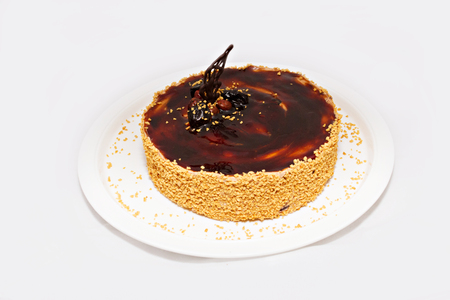 strew: Chocolate cake with nuts and yellow strew on white plate