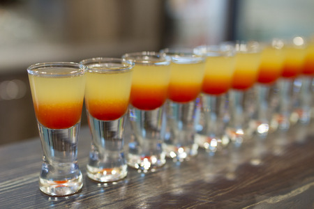 shooters: Set of cocktail shots on a wooden bar counter