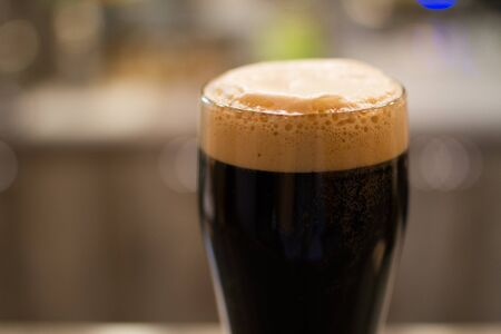 pint: Glass - pint- of dark beer with foam Stock Photo