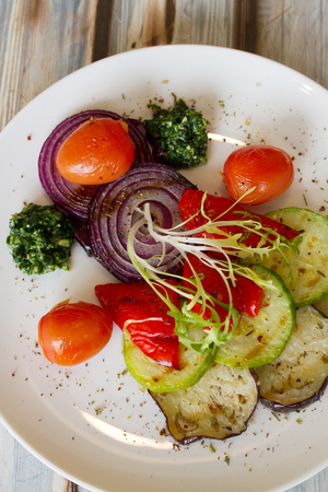 Gilled vegetables salad served on a plate - tomatoes, zucchini, onion, eggplant