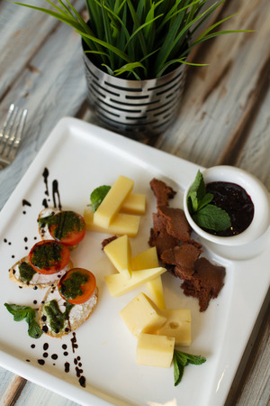 collation: Cheese and tomato appetizer or cold collation with green leaves and sauce on a wooden table