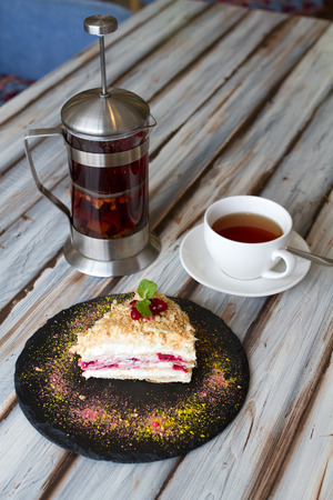 A cup of tea and a french press with black tea and a piece of cake on a wooden table Stock Photo