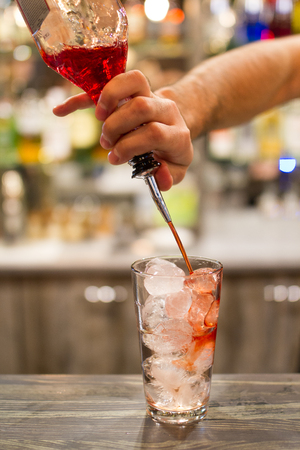 A barmans hand who making a red coctail