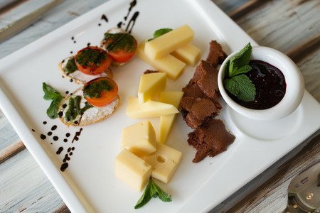 Cheeseplate with souce and bread on a wooden table