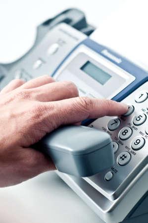 repondre au telephone: Tube gris de t�l�phone-fax dans la main d'un homme.