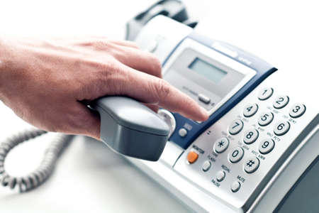 Graue Rohr über Telefon-Fax in die Hand eines Mannes.