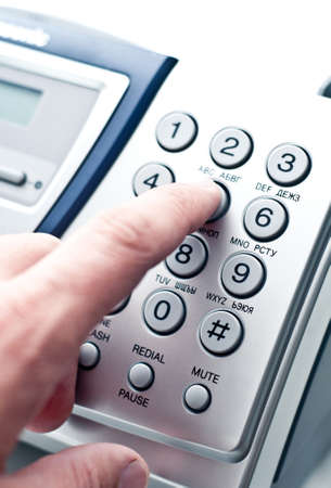 Hand dialing number on phone or fax machine. photo