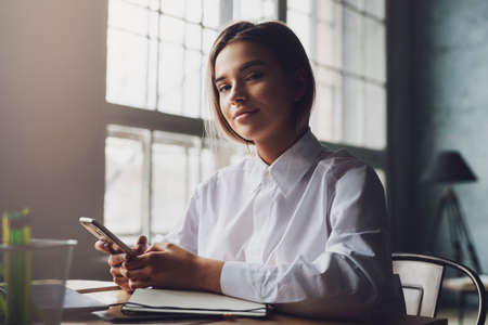 Young female sitting at desk, using smartphone for Internet communication. Pretty girl chatting in online messenger Stock Photo