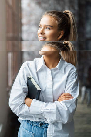Student girl in a white shirt smiles and stands near the window. Portrait of incredibly attractive woman in office