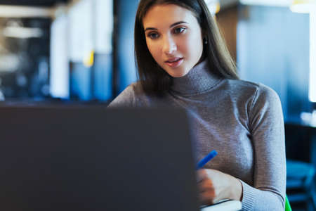 Business woman sitting at table working on project. Young beautiful woman sits at a table in a cafe and uses a computer for telecommuting. Female communicates with friends.