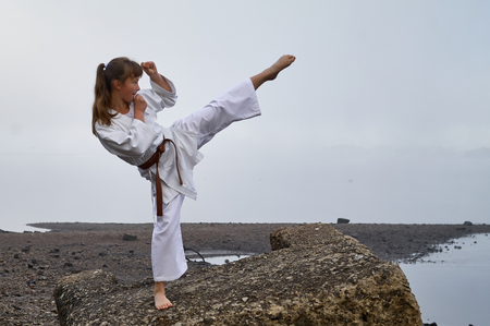 Young Woman in Kimono practicing karate, Japanese martial arts on river coast. Early foggy morning Stock Photo