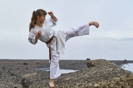 Young Woman in Kimono practicing karate, Japanese martial arts on river coast. Early foggy morning