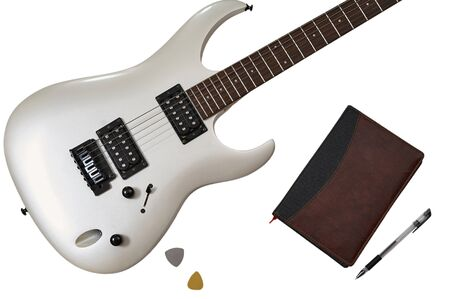 Workspace of musician: guitarist, composer or song writer. Top view of closeup of white electric guitar, two mediators, close notebook and pen. Imagens