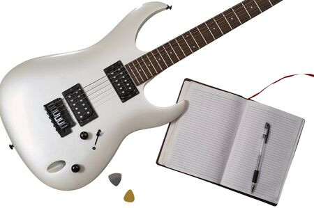 Workspace of musician: guitarist, composer or song writer. Top view of closeup of white electric guitar, two mediators, open notebook and pen.