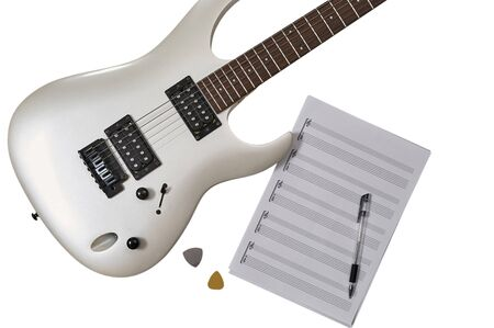 Workspace of musician: guitarist, composer or song writer. Top view of closeup of white electric guitar, two mediators, notes&tabs stuff and pen. Imagens