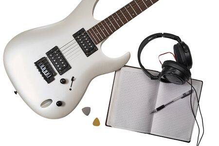 Workspace of musician: guitarist, composer or song writer. Top view of closeup of white electric guitar, two mediators, open notebook, pen and headphones. Imagens