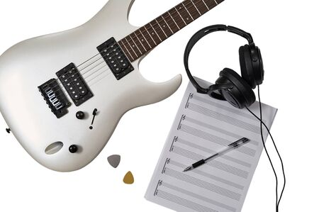 Workspace of musician: guitarist, composer or song writer. Top view of closeup of white electric guitar, two mediators, music paper for notes and guitar tabs, pen and headphones. Imagens