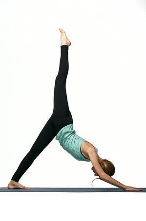 Portrait of young cheerful slim sporty beautiful woman working out on mat, warming up, doing exercises, isolated studio image on white background