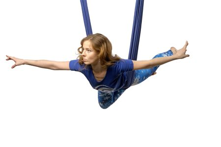 Young woman practices aerial anti-gravity yoga with a hammock in a white studio. Concept of a mental and physical health an harmony living
