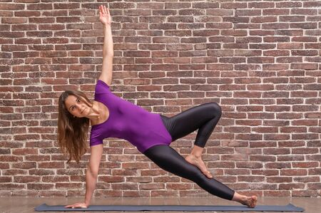 Sporty attractive young woman practicing yoga exercise, working out, wearing sportswear, full length, brick wall background