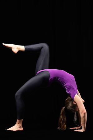 Beautiful young fit woman with slim muscular body in sportswear doing yoga exercise. Full length, side view, studio shot, black background