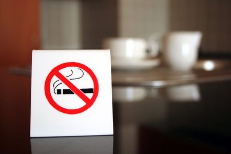 displayed: A white no smoking sign displayed on a table in a cafe
