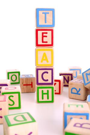 numeracy: Childrens colored blocks spelling the word teach and surrounded by other blocks - has clipping path