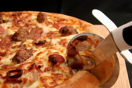 Pizza cutter slicing through a meat lovers deep pan